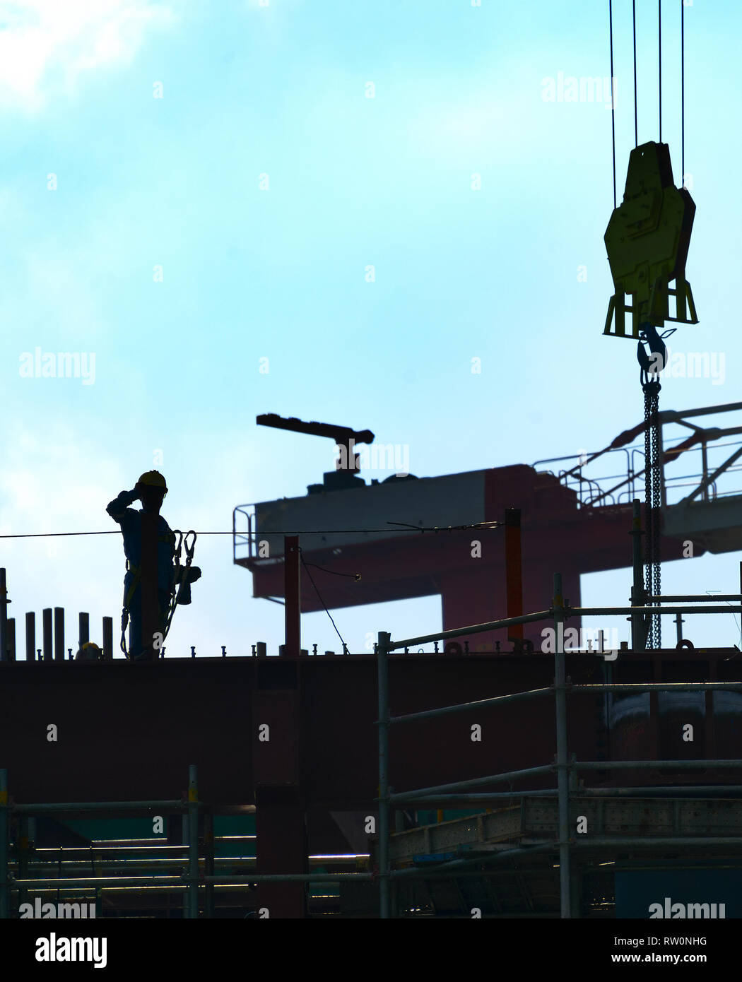 Silhouette of construction worker at construction site. Cranes - Stock Image