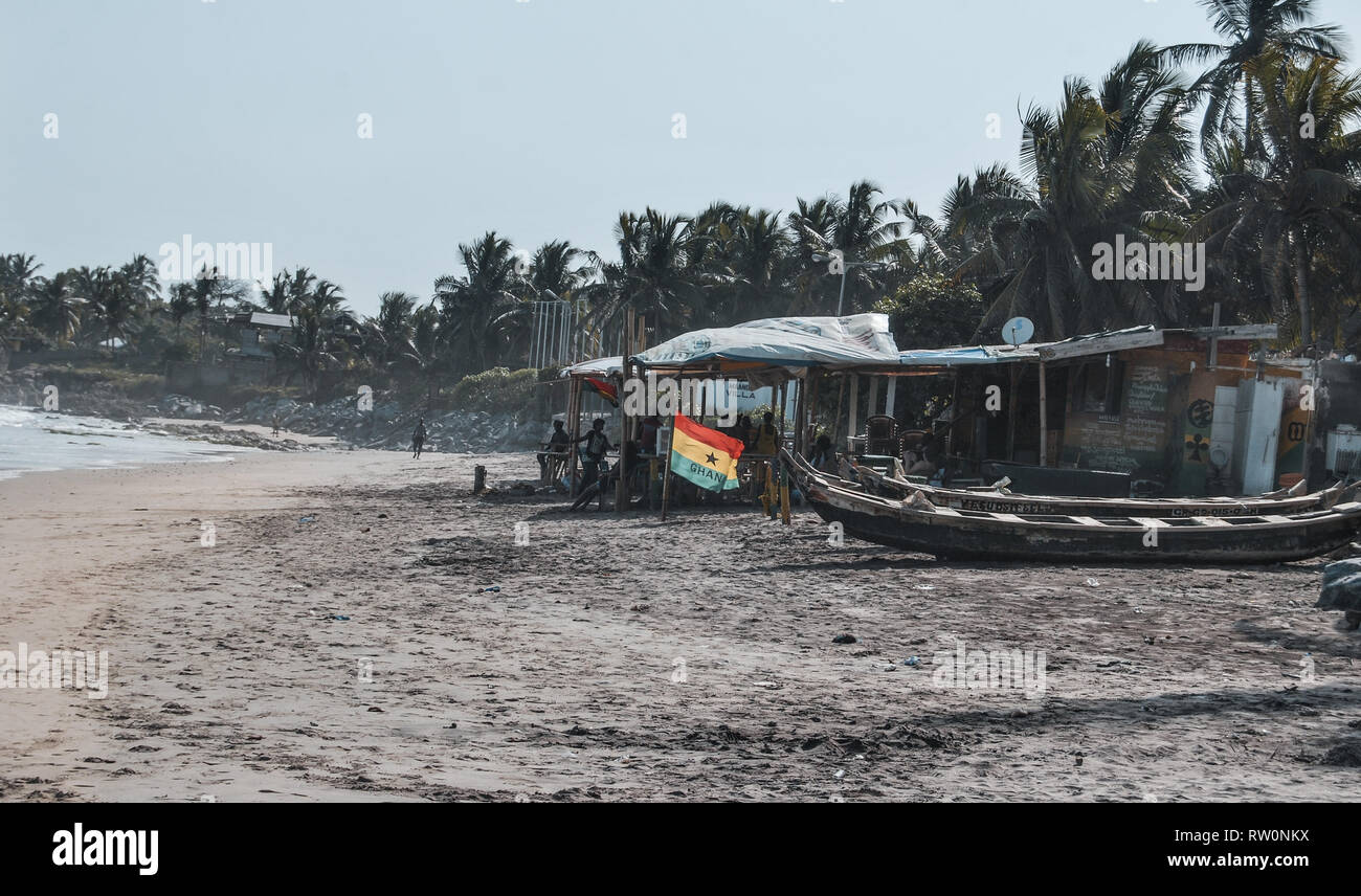 A nice landscape photo of colorful Ghanaian flag on the background of a beautiful tropical rain forest. Local wooden boats are docked on the beach. - Stock Image