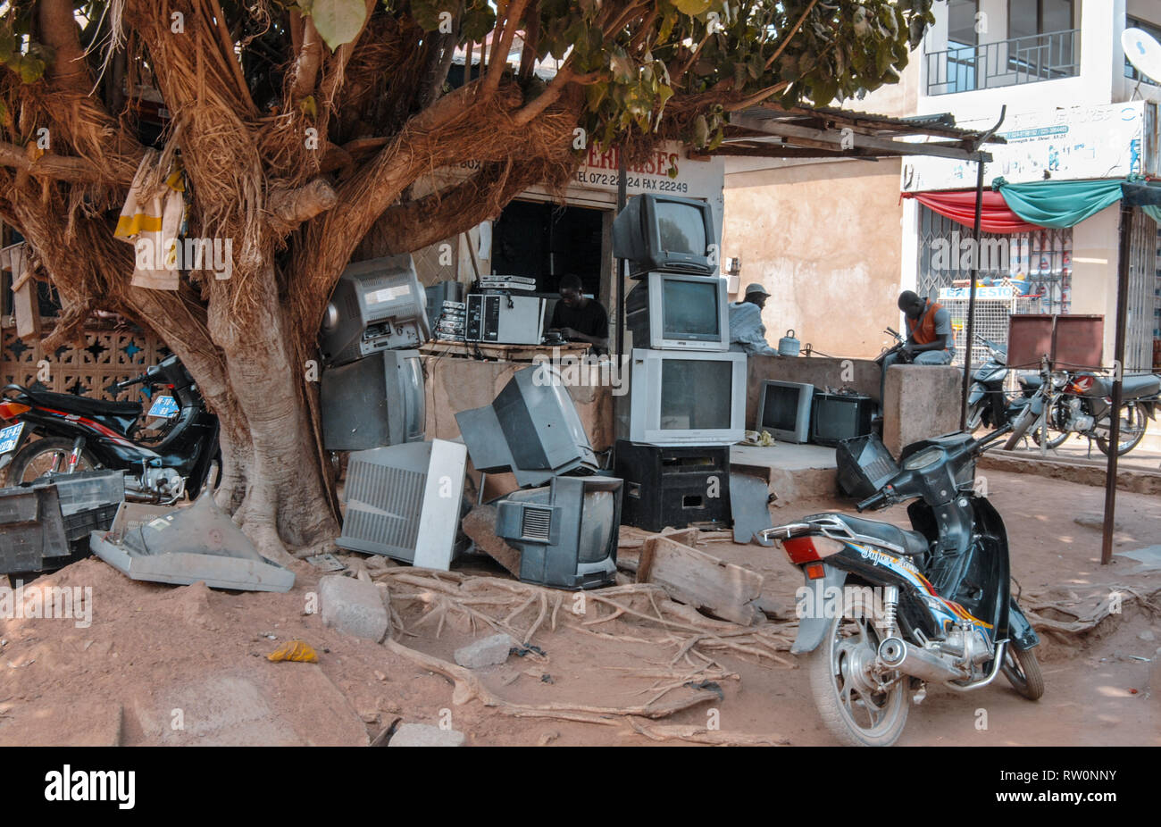 A pile of old tvs (television sets) in front of a tv repair shop in Bolgatanga, Ghana, West Africa - Stock Image