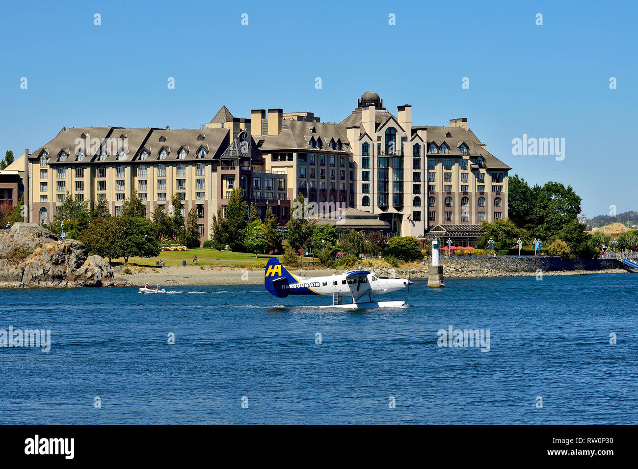 A horizontal image of the Delta Hotel on the shore of the inner harbour in Victoria, Vancouver Island with a commuter float plane taxing by on the wat - Stock Image