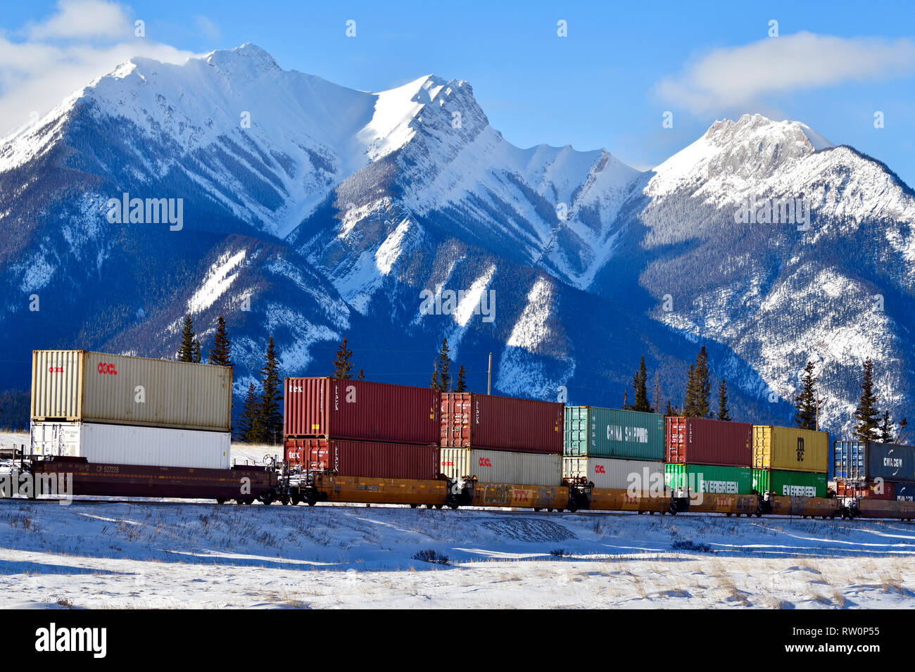 A Canadian National freight train hauling a load og container cars through the snow-capped rocky mountain of Alberta Canada. - Stock Image