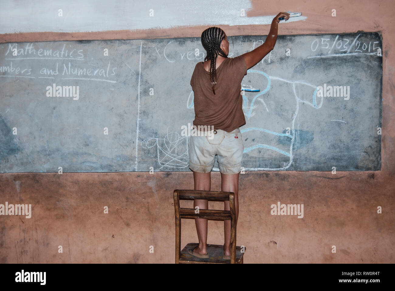 A woman with afro braids is painting a wall of a local elementary school in Ghana, Africa - Stock Image