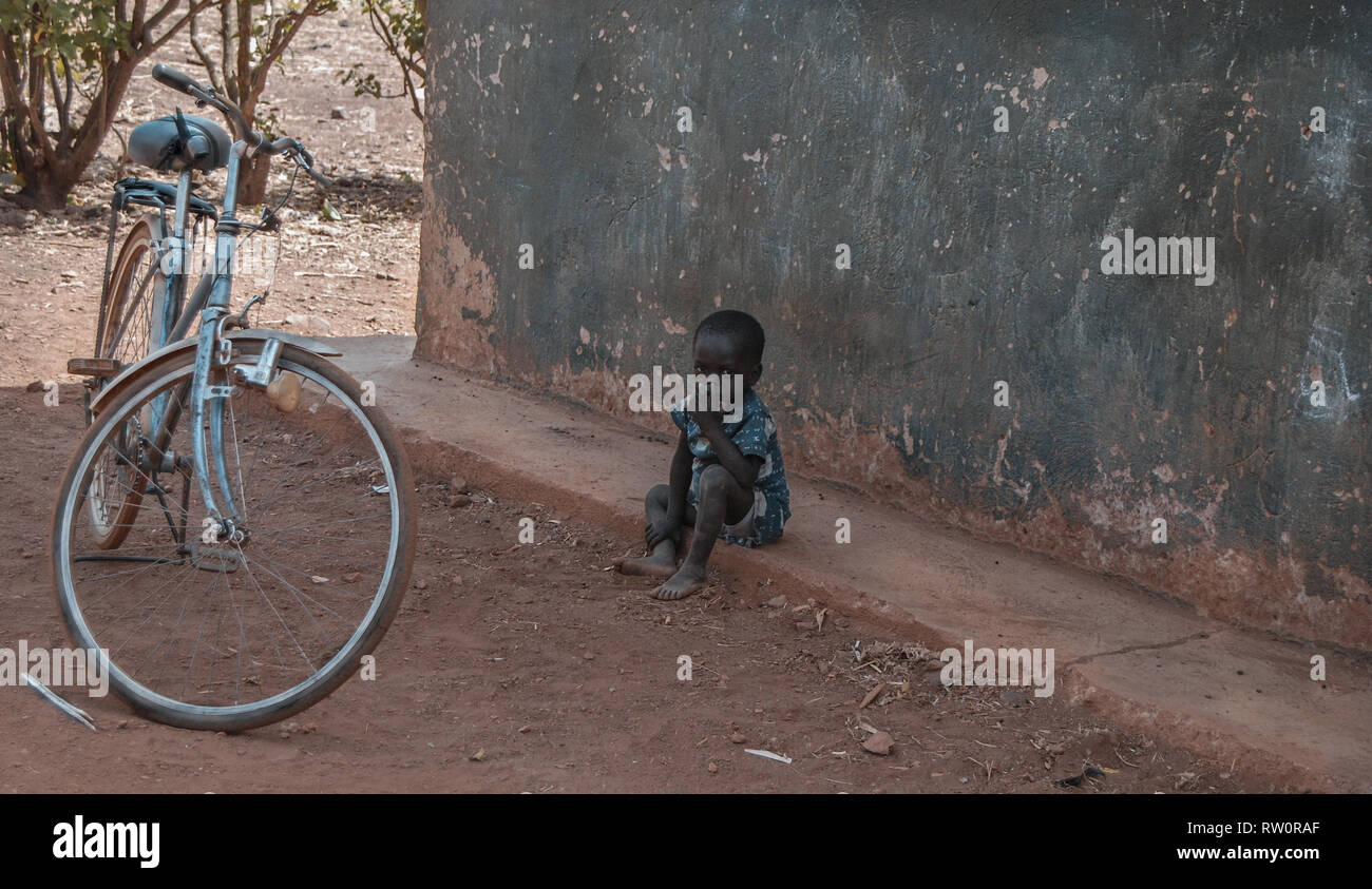 A young serious looking Ghanaian boy sitting outside his home. There is a blue bicycle parked outside. - Stock Image
