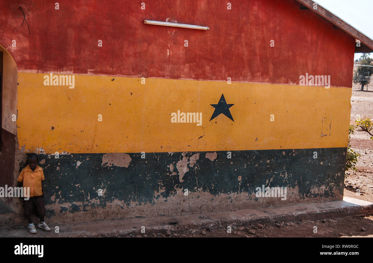 A boy posing on the background of a house wall painted in the colors of Ghanaian flag - red, yellow and green. - Stock Image