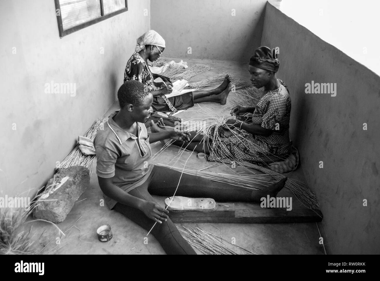 A black and white photo of local Ghanaian women weaving the famous Bolga (Bolgatanga) handwoven market baskets at their home in Kongo village, Ghana. - Stock Image