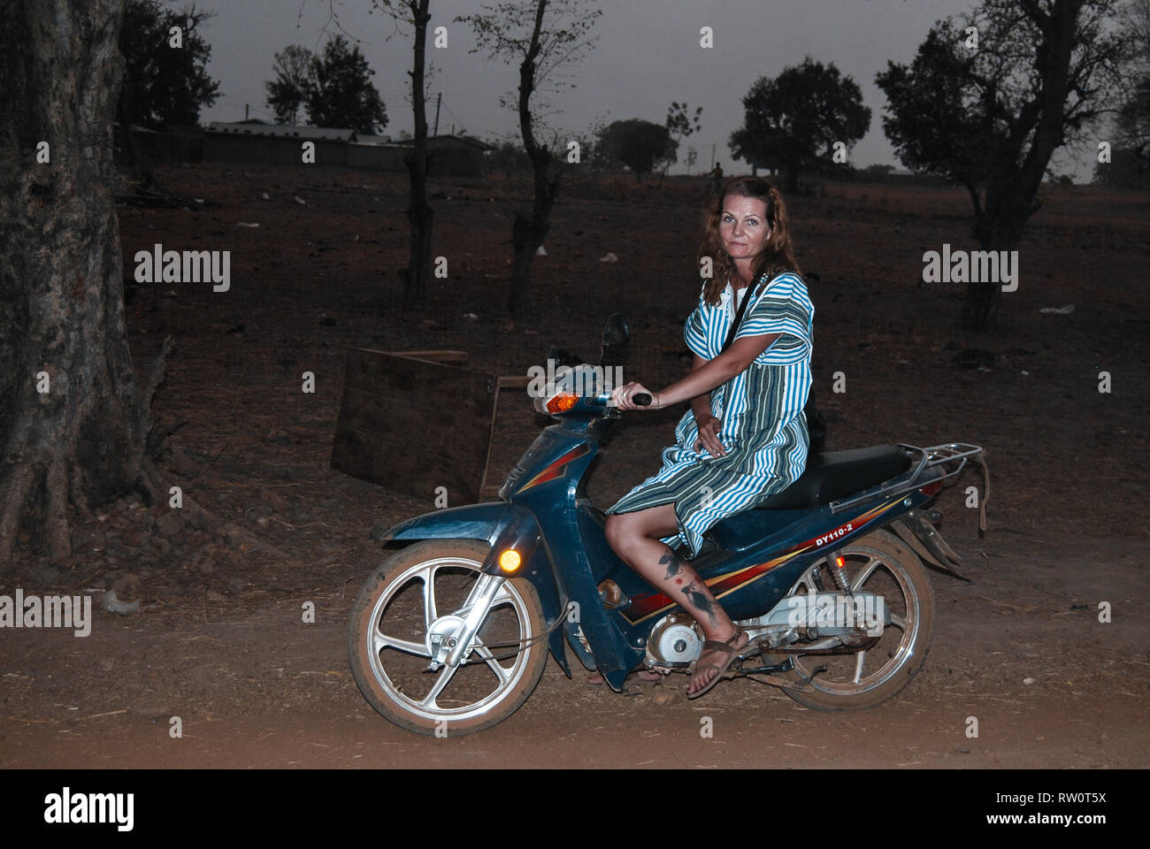A caucasian woman wearing traditional Ghanaian clothes is posing on a blue scooter during the night time in a savanna - Stock Image
