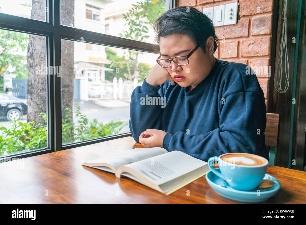 Asian woman reading book in the library - Stock Image