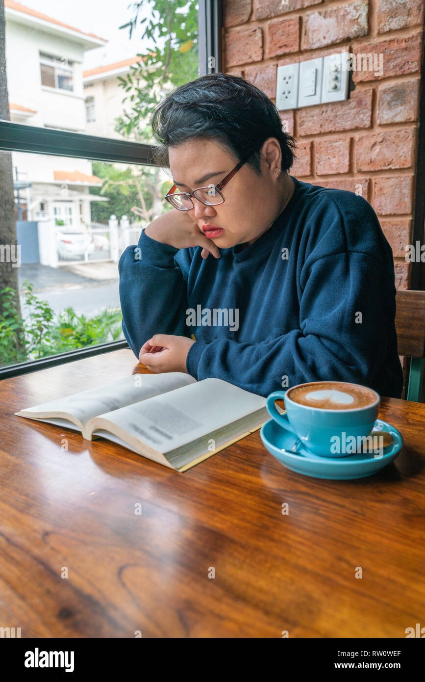 Vertical photo of Asian girl reading book and drinking coffee - Stock Image