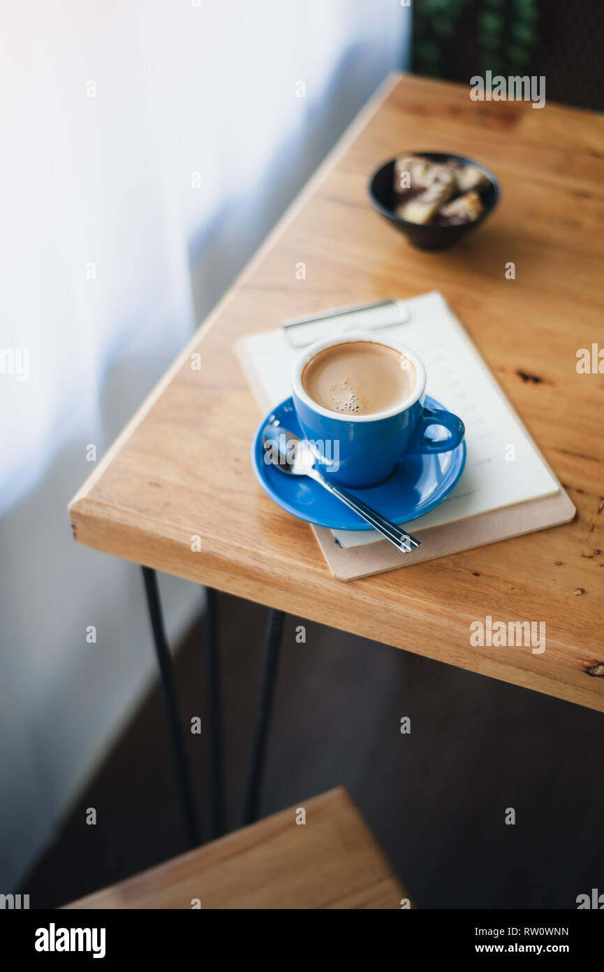 Abstract emotional scene of hot Long black (Americano) in blue coffee cup on table at cafe in morning time. Weekend activity and relaxation. favorite  - Stock Image