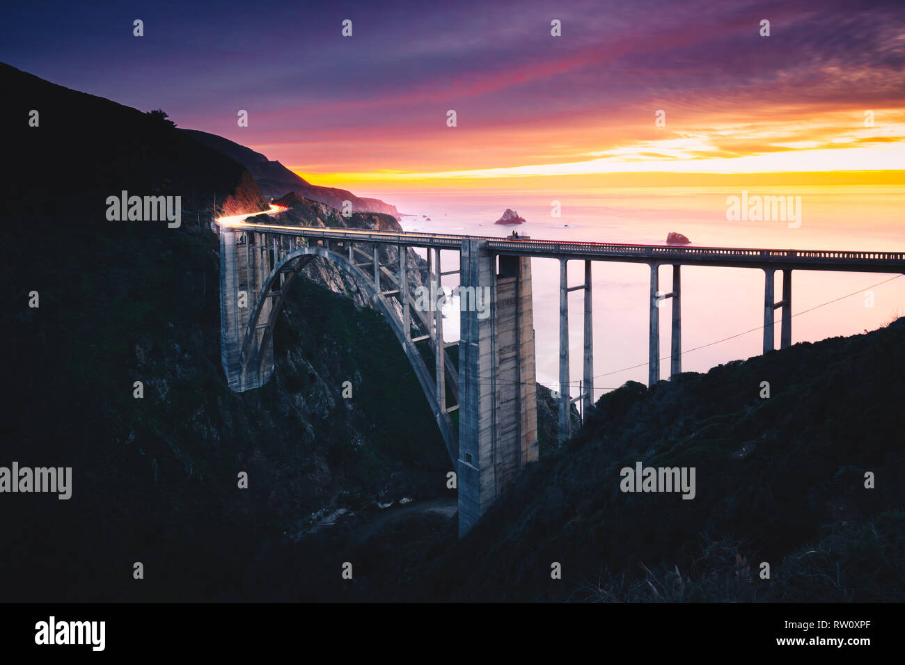 Bixby Creek Bridge with Colorful Sunset and Car Light Trails, Big Sur, CA - Stock Image
