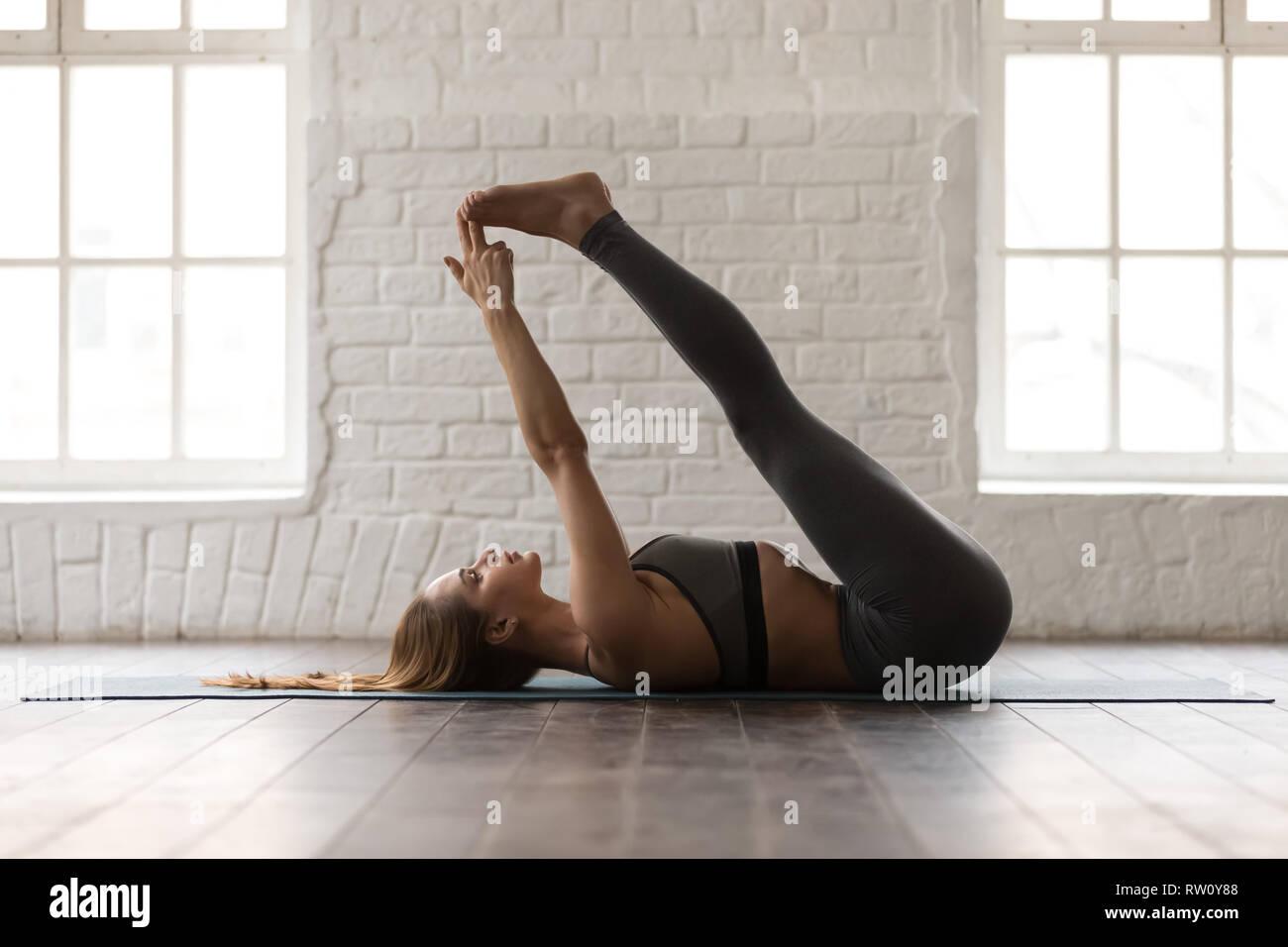 Woman practicing yoga, Double Leg Lift exercise, Urdhva Prasarita Padasana - Stock Image