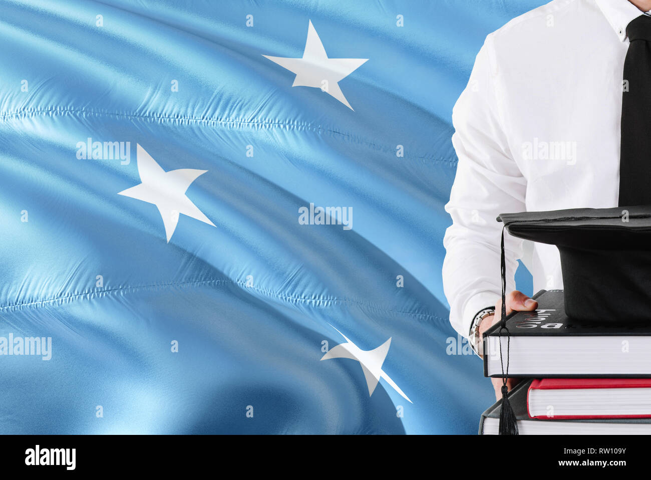 Successful Micronesian student education concept. Holding books and graduation cap over Micronesia flag background. - Stock Image