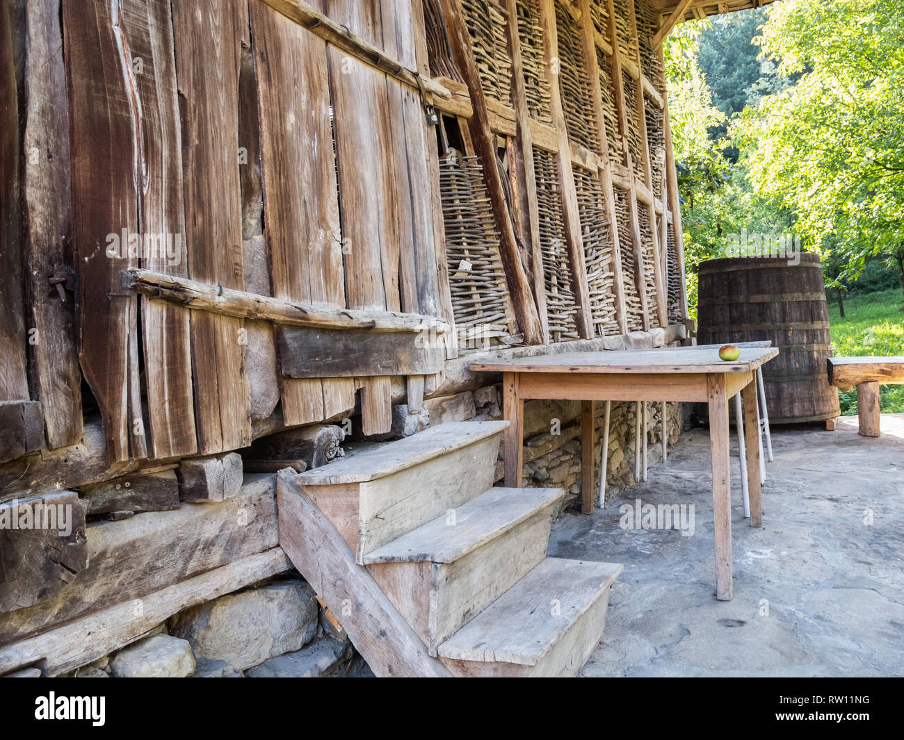 Part of an old wooden barn with a barrel and table with an apple on it in front, at Baba Stana Neighborhood, Oreshak, Bulgaria - Stock Image