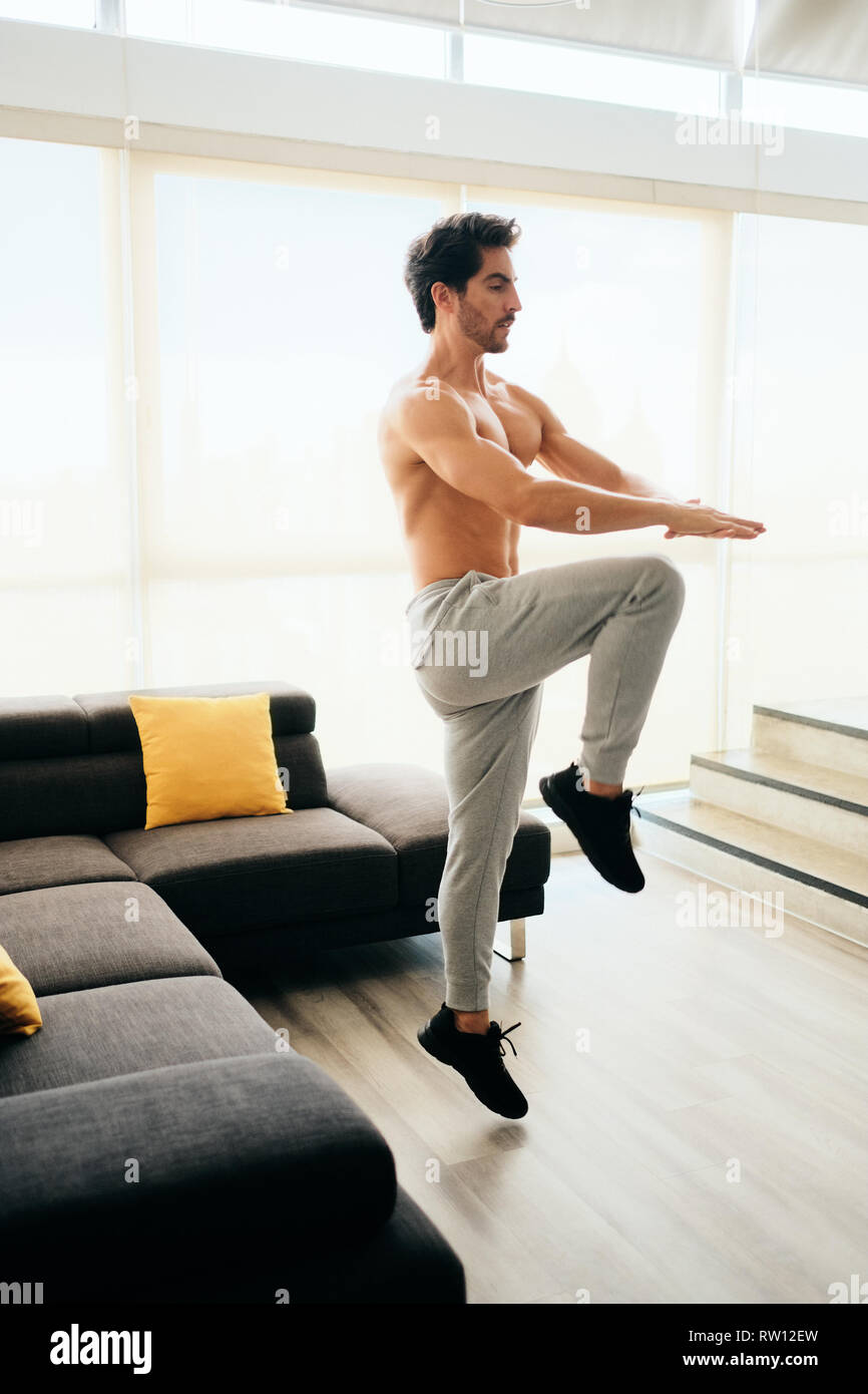 Fit young white man training at home. Handsome hispanic male athlete working out for wellbeing in domestic gym, training abdomen and legs muscles with - Stock Image