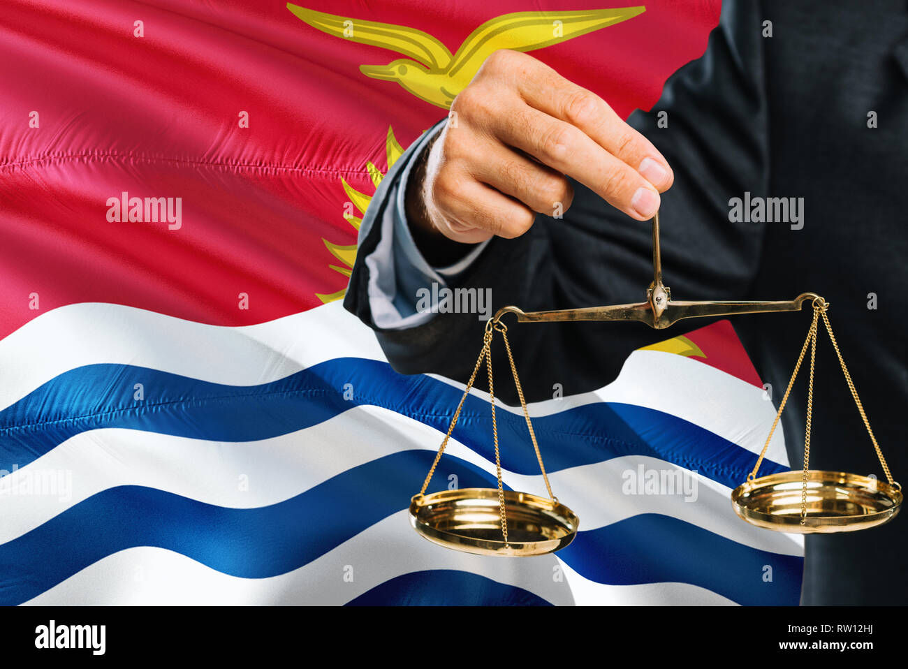 Judge is holding golden scales of justice with Kiribati waving flag background. Equality theme and legal concept. Stock Photo