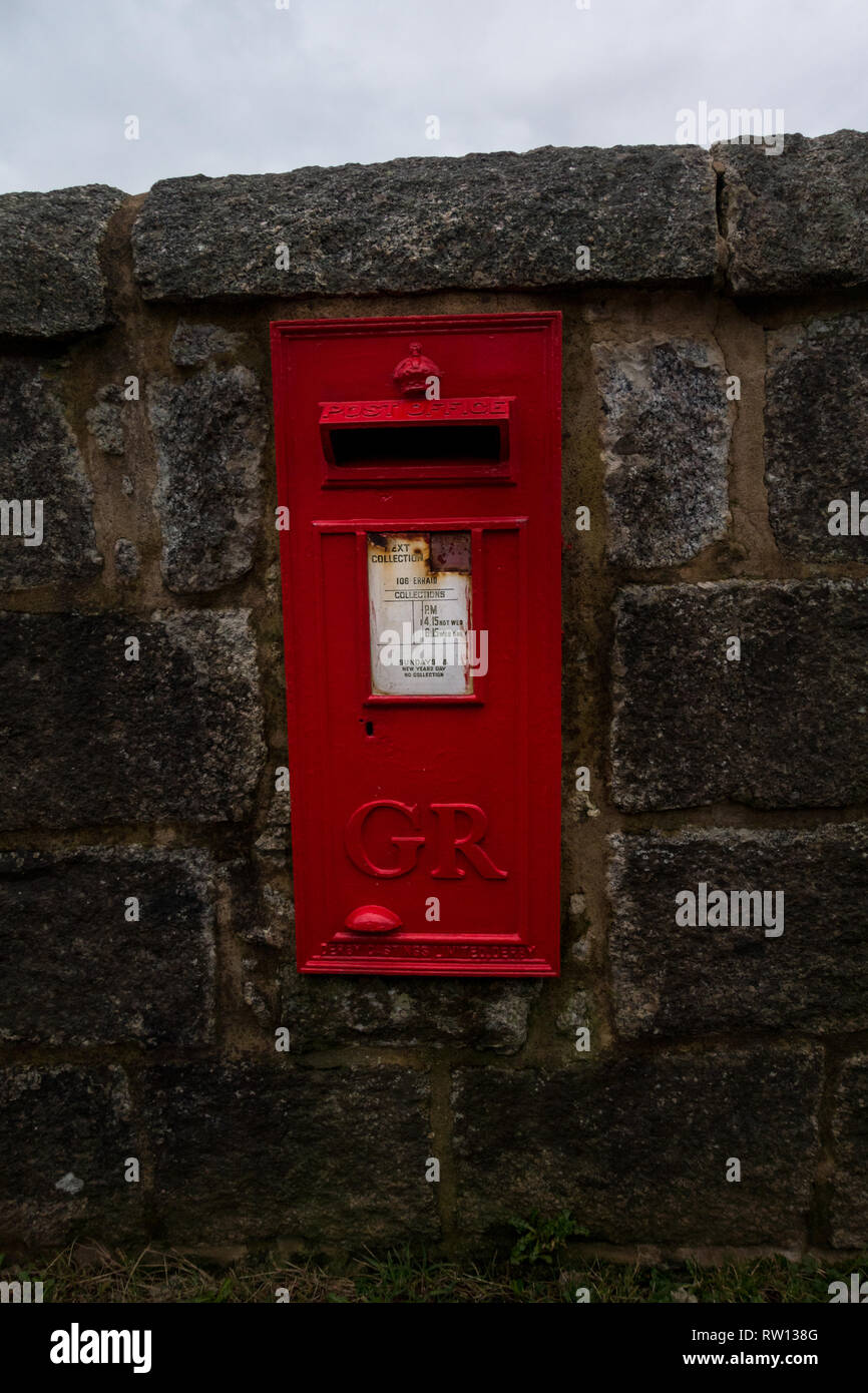 Remote red Royal Mail post box with the letters GR (for George Rex - King George) on the Isle of Erraid, Isle of Mull, Scotland Stock Photo