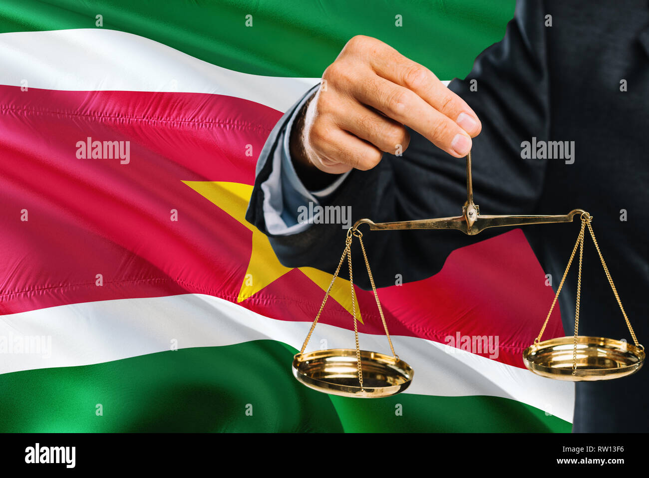 Surinamese Judge is holding golden scales of justice with Suriname waving flag background. Equality theme and legal concept. - Stock Image