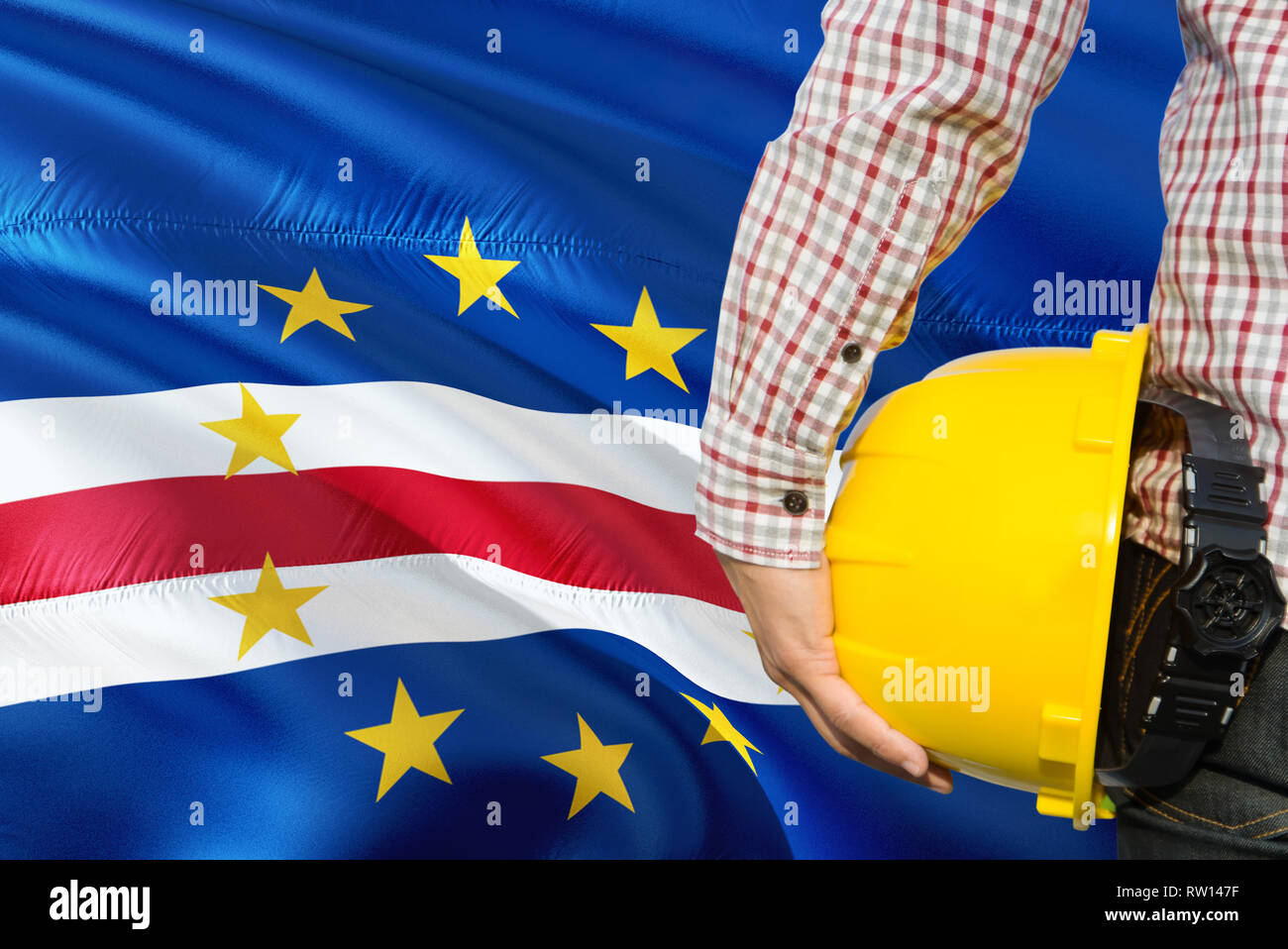 Engineer is holding yellow safety helmet with waving Cape Verde flag background. Construction and building concept. - Stock Image