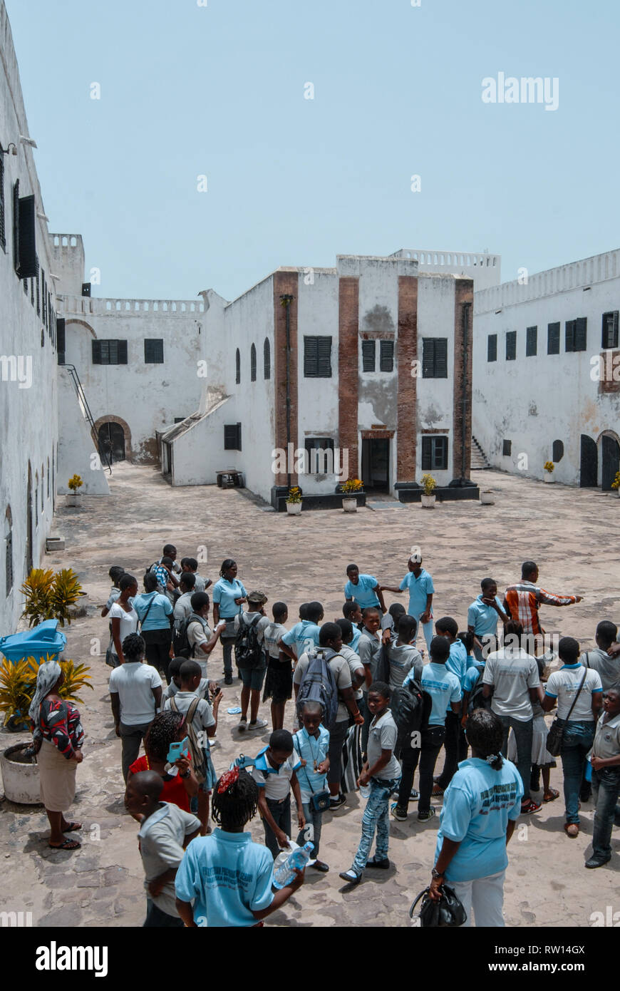 A nice photo of local Ghanaian school students visiting the old historic Elmina slave castle at the coast of Ghana, West Africa - Stock Image