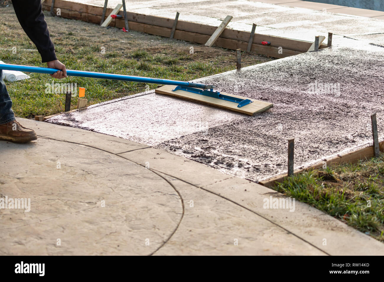 Construction Worker Smoothing Wet Cement With Trowel Tool