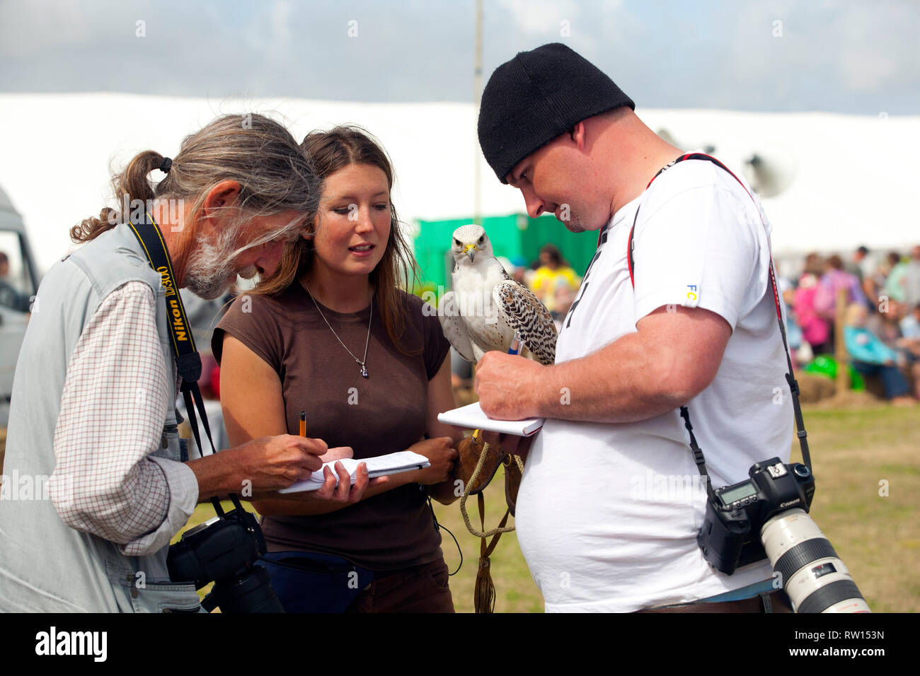 Local newspaper Photographers at local agricultural, show, captioning, writing, interview, notes, story, falconer, falcon, Chale, Isle of Wight - Stock Image