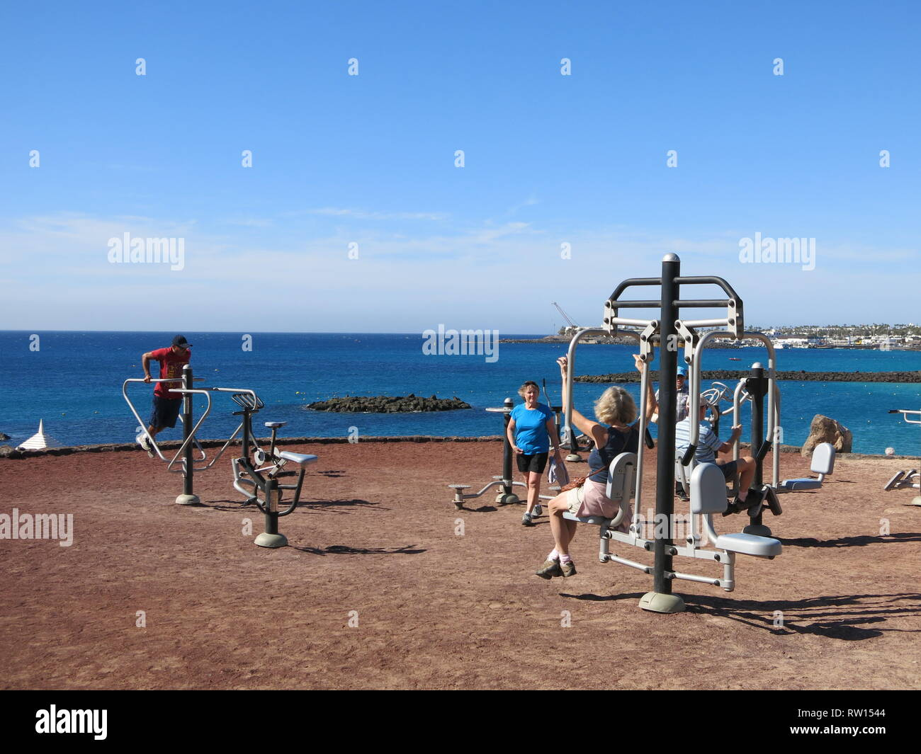 People enjoying a range of outdoor exercise equipment on the shoreline at Playa Blanca, Lanzarote; keep fit in the fresh air and sunshine. - Stock Image