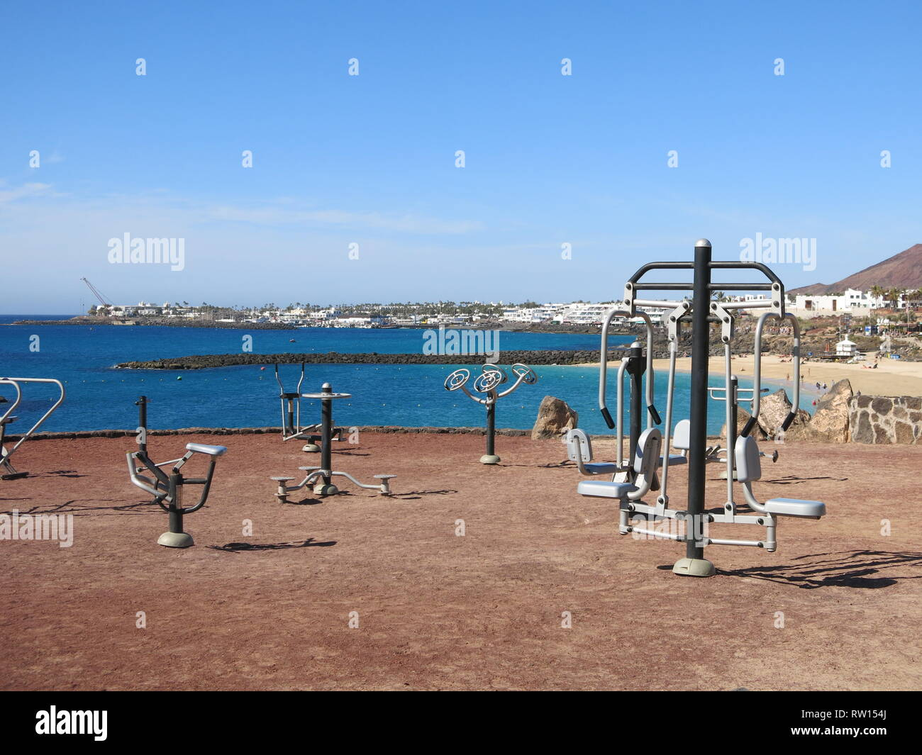 A range of outdoor exercise equipment on the shoreline at Playa Blanca, Lanzarote; keep fit in the fresh air and sunshine whilst admiring the view. - Stock Image