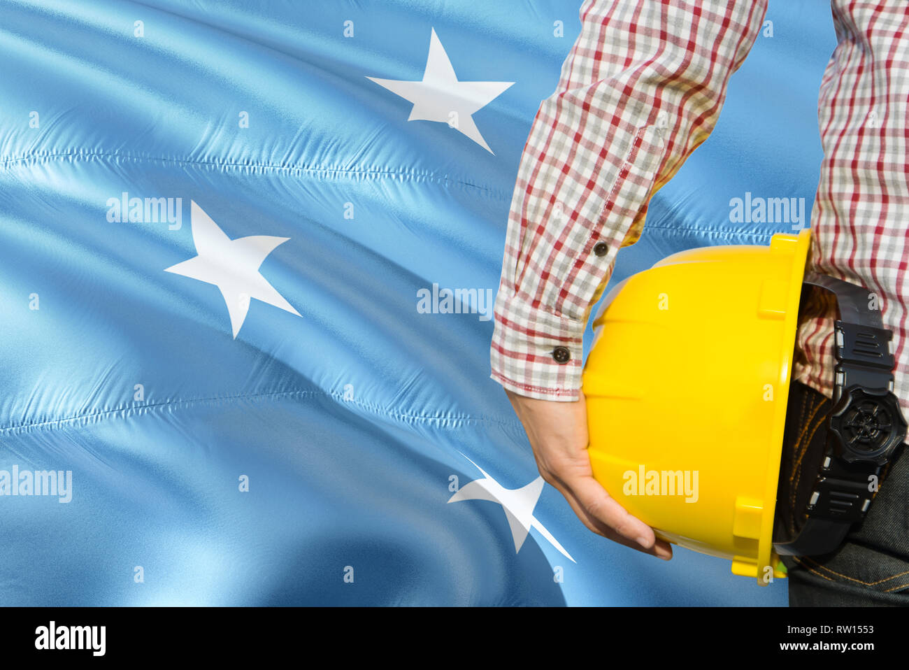 Micronesian Engineer is holding yellow safety helmet with waving Micronesia flag background. Construction and building concept. - Stock Image