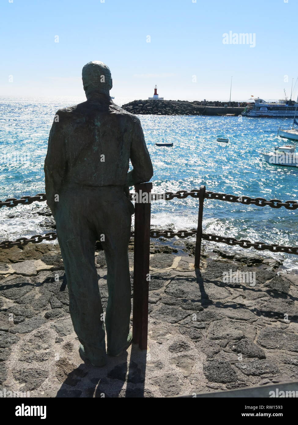 A statue of a man gazing out to sea on the harbour wall at Playa Blanca is to commemorate early Canarians who contributed to the island's development - Stock Image