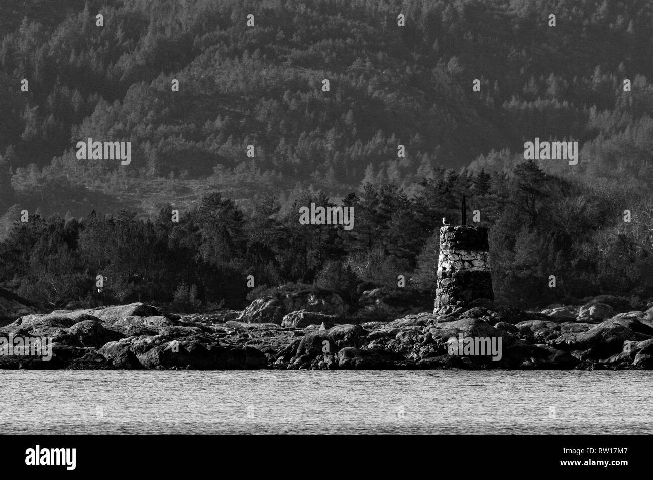 Old stone landmark (cairn) for ships' navigation around the many islands in Raunefjorden, outside of Bergen, Norway - Stock Image