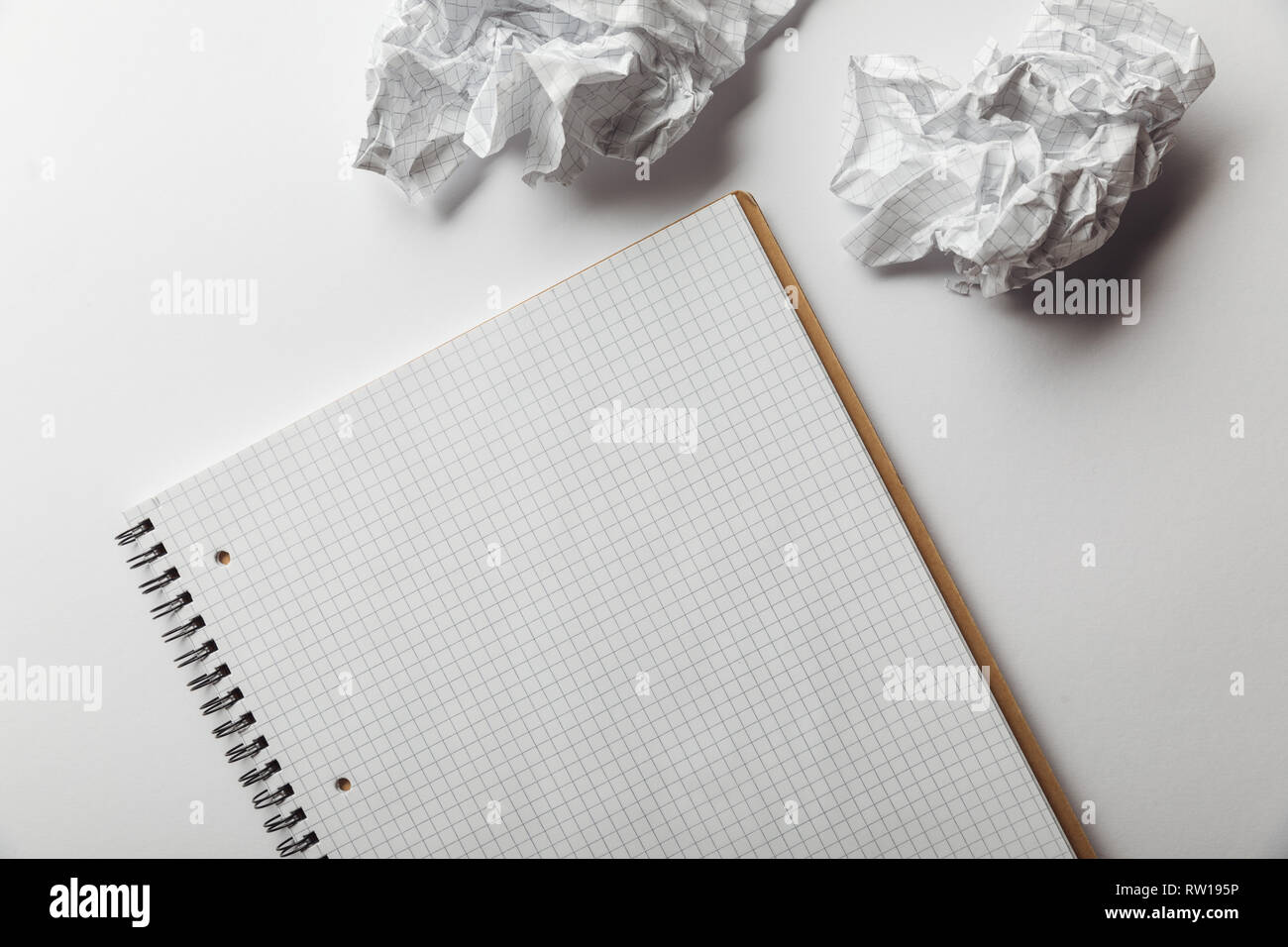 top view of notebook with blank squared page near crumpled sheets on white background - Stock Image
