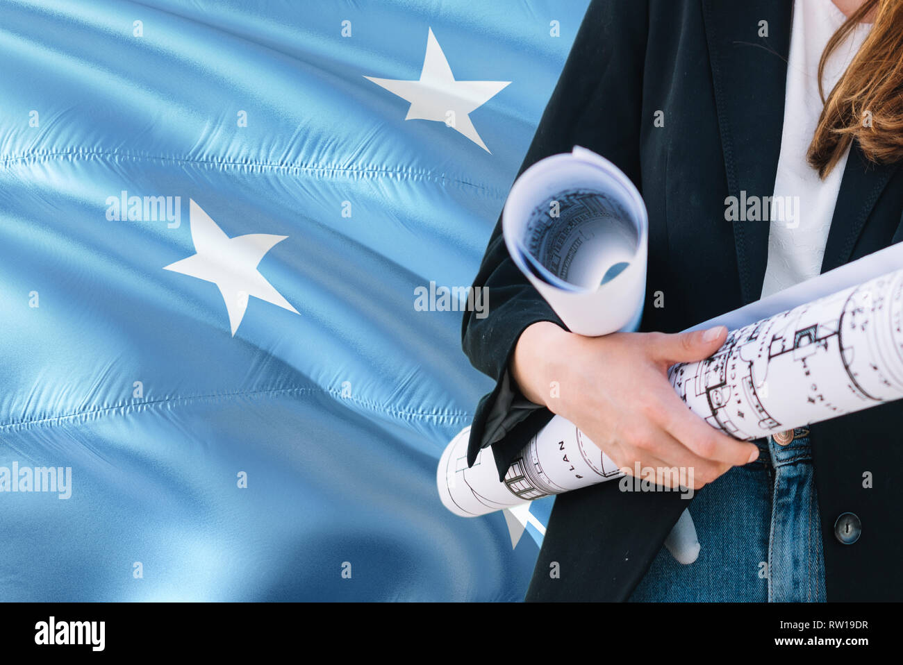 Micronesian Architect woman holding blueprint against Micronesia waving flag background. Construction and architecture concept. - Stock Image