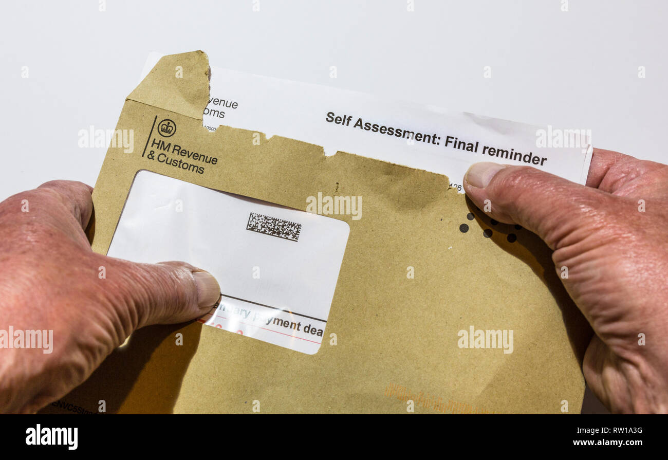 Opening a final reminder letter from HM Revenue & Customs  for paying tax. - Stock Image