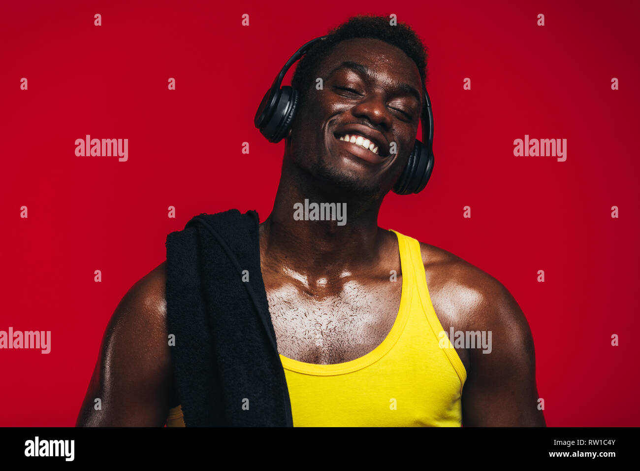 African man with towel on shoulder enjoying listening to music on headphones. Fit young man listening to music during workout break on red background. - Stock Image