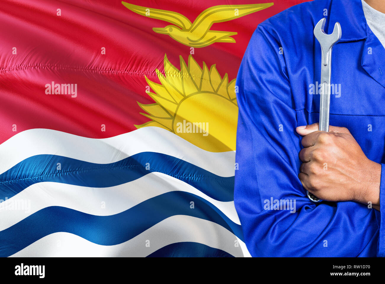 Mechanic in blue uniform is holding wrench against waving Kiribati flag background. Crossed arms technician. - Stock Image
