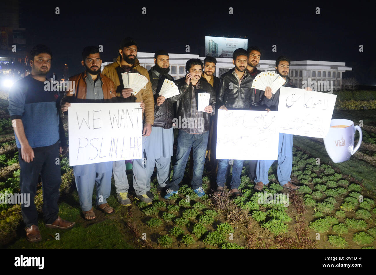 Pakistani cricket lovers hold placards and tickets during