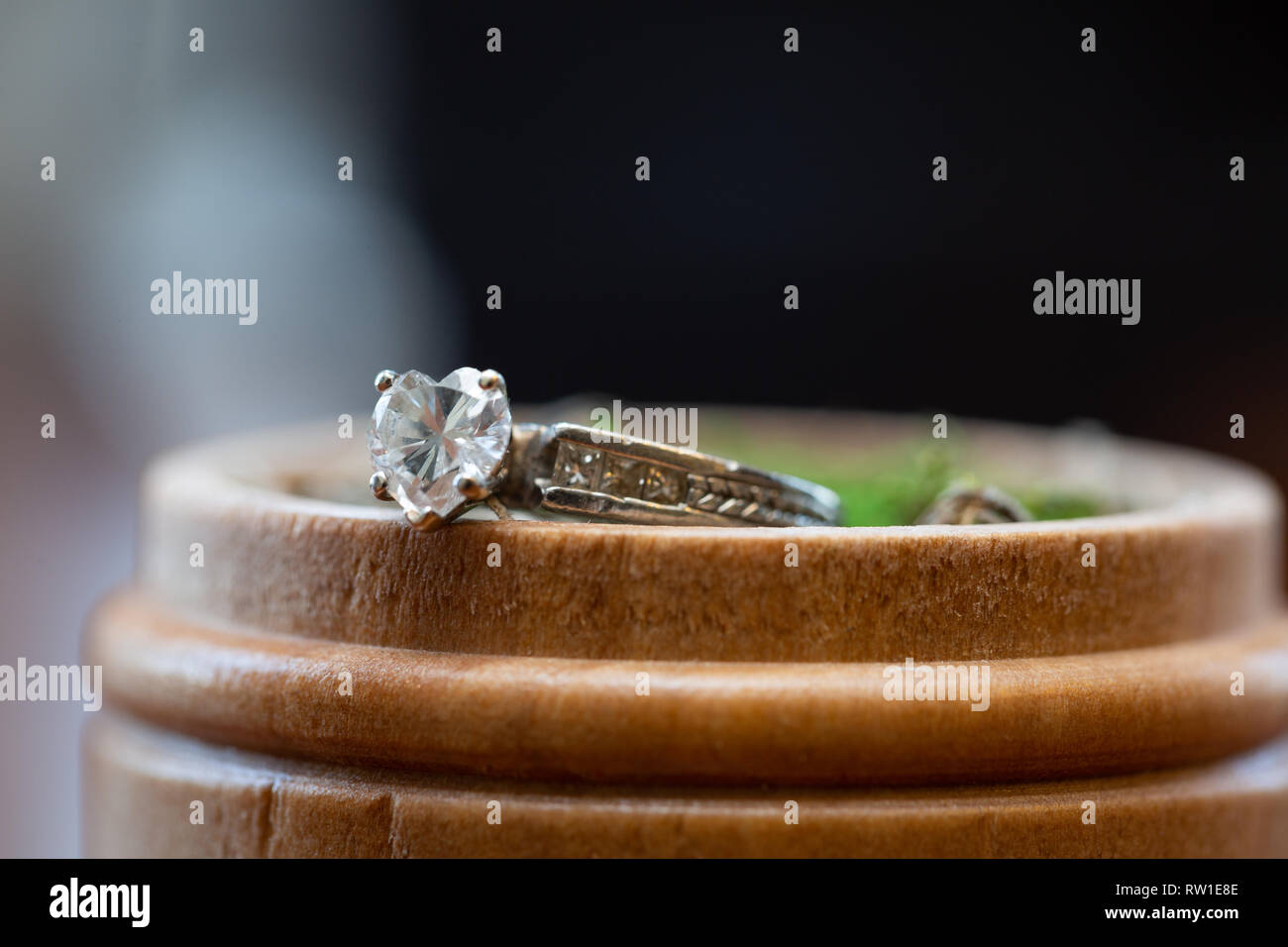 Macro photo of an engagement ring on a wooden box - Stock Image