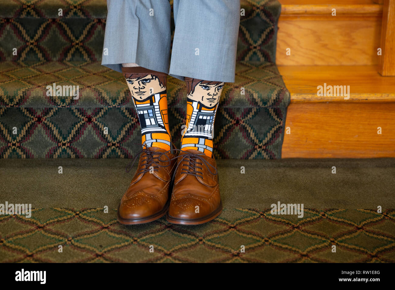 Groom on wedding day showing styled Luke Skywalker-themed socks with brown shoes and grey pants - Stock Image