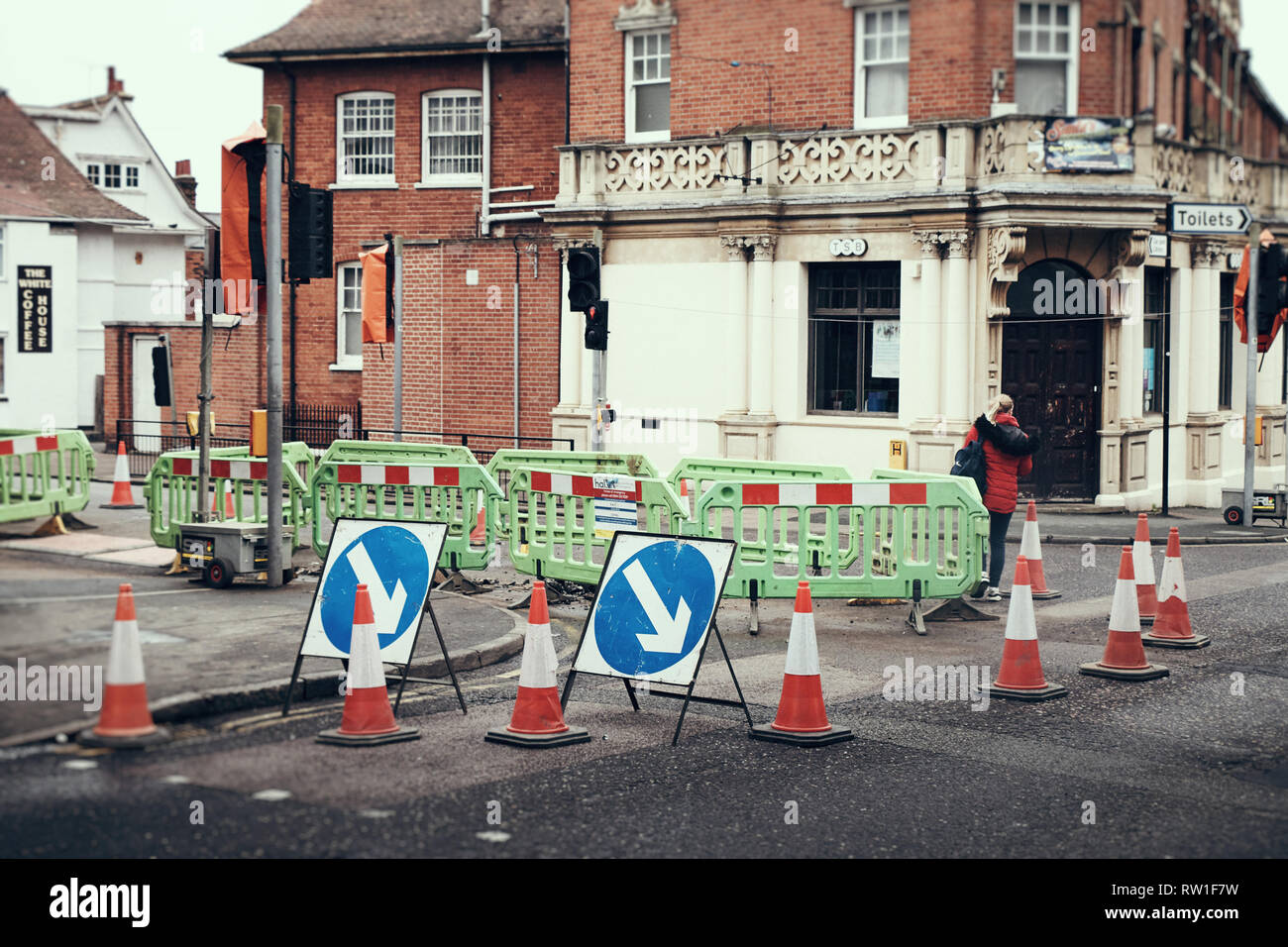 Harwich & Dovercourt, Essex, ENGLAND - March 3, 2019: Roadworks, barriers and cones at the traffic lights in Harwich high street with a woman walking  - Stock Image