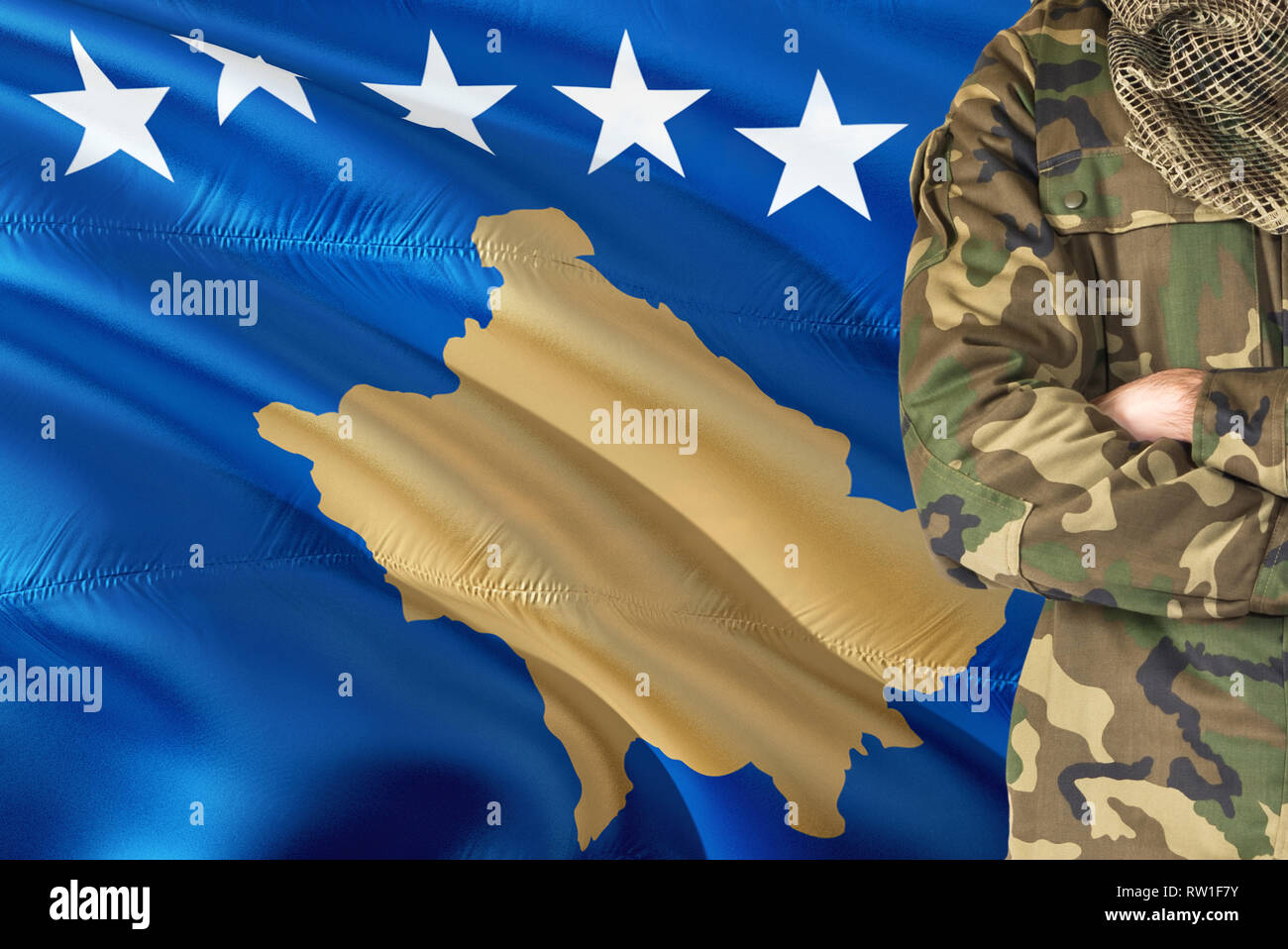 Crossed arms soldier with national waving flag on background - Kosovo Military theme. Stock Photo