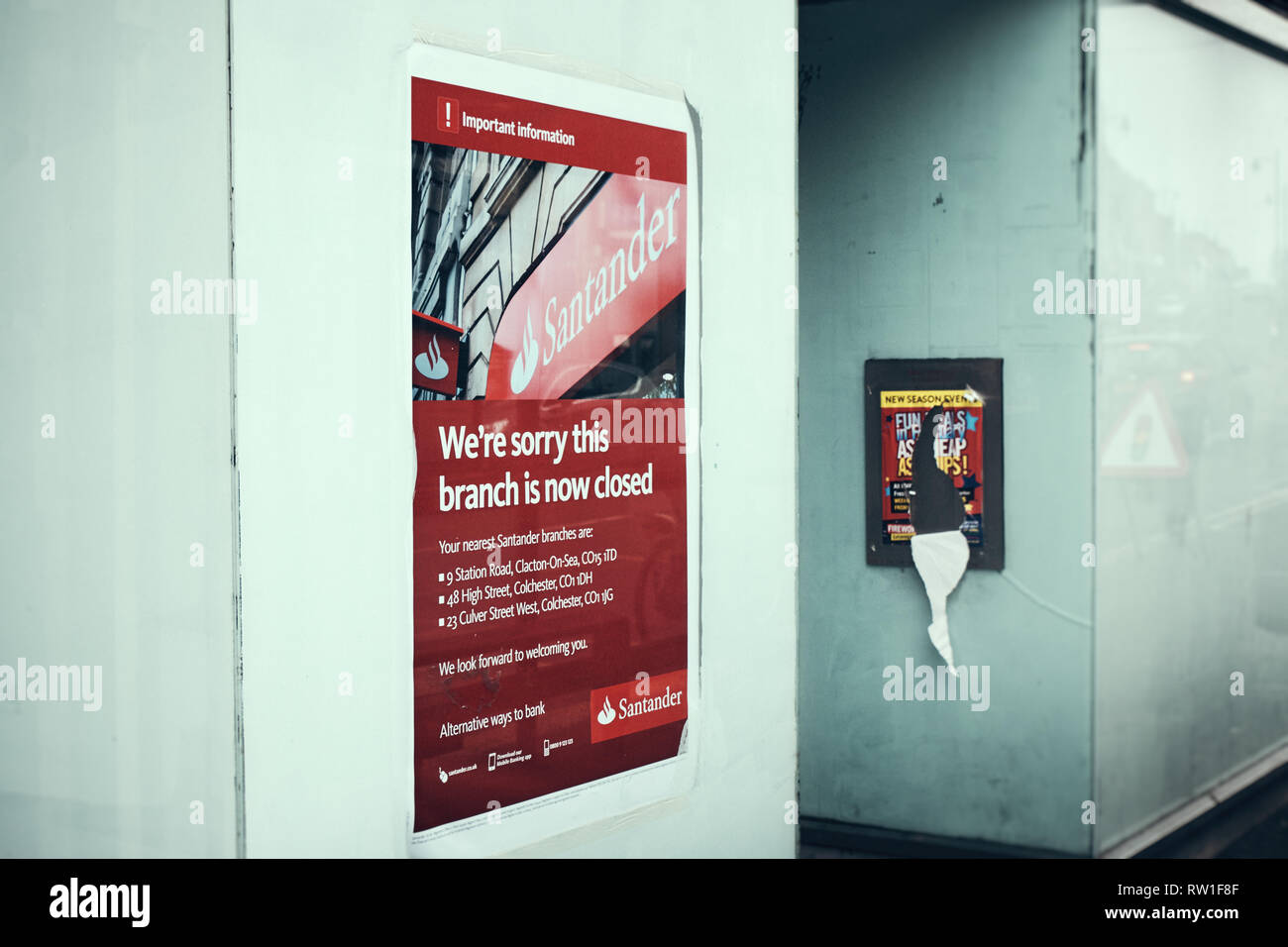 Harwich & Dovercourt, Essex, ENGLAND - March 3, 2019: Side view of a poster informing of the branch closure for Santander in Harwich High Street with  - Stock Image