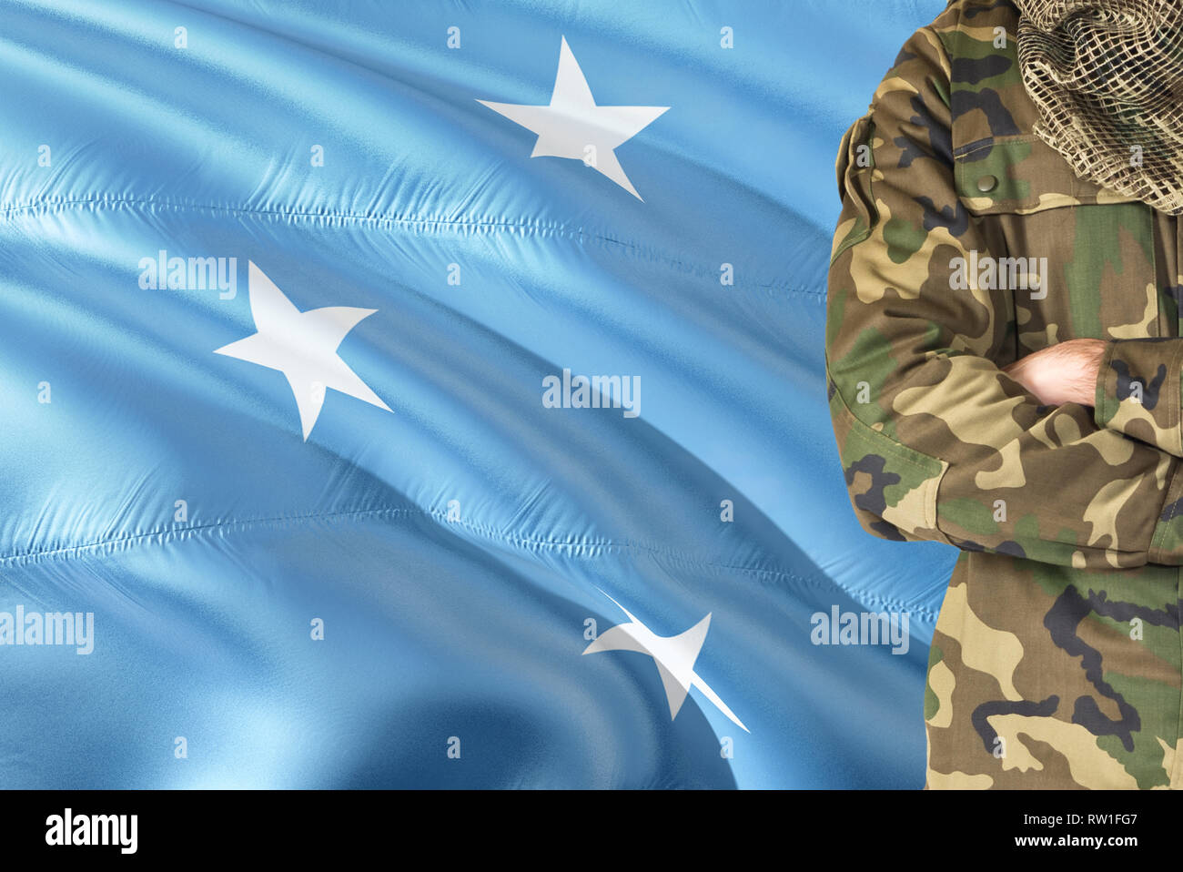 Crossed arms Micronesian soldier with national waving flag on background - Micronesia Military theme. - Stock Image