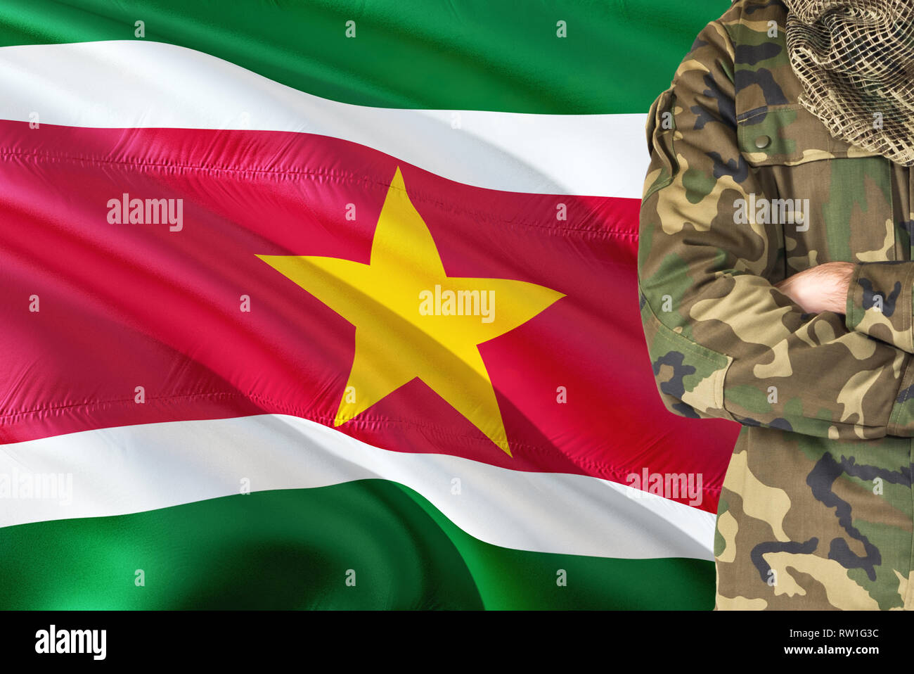 Crossed arms Surinamese soldier with national waving flag on background - Suriname Military theme. - Stock Image