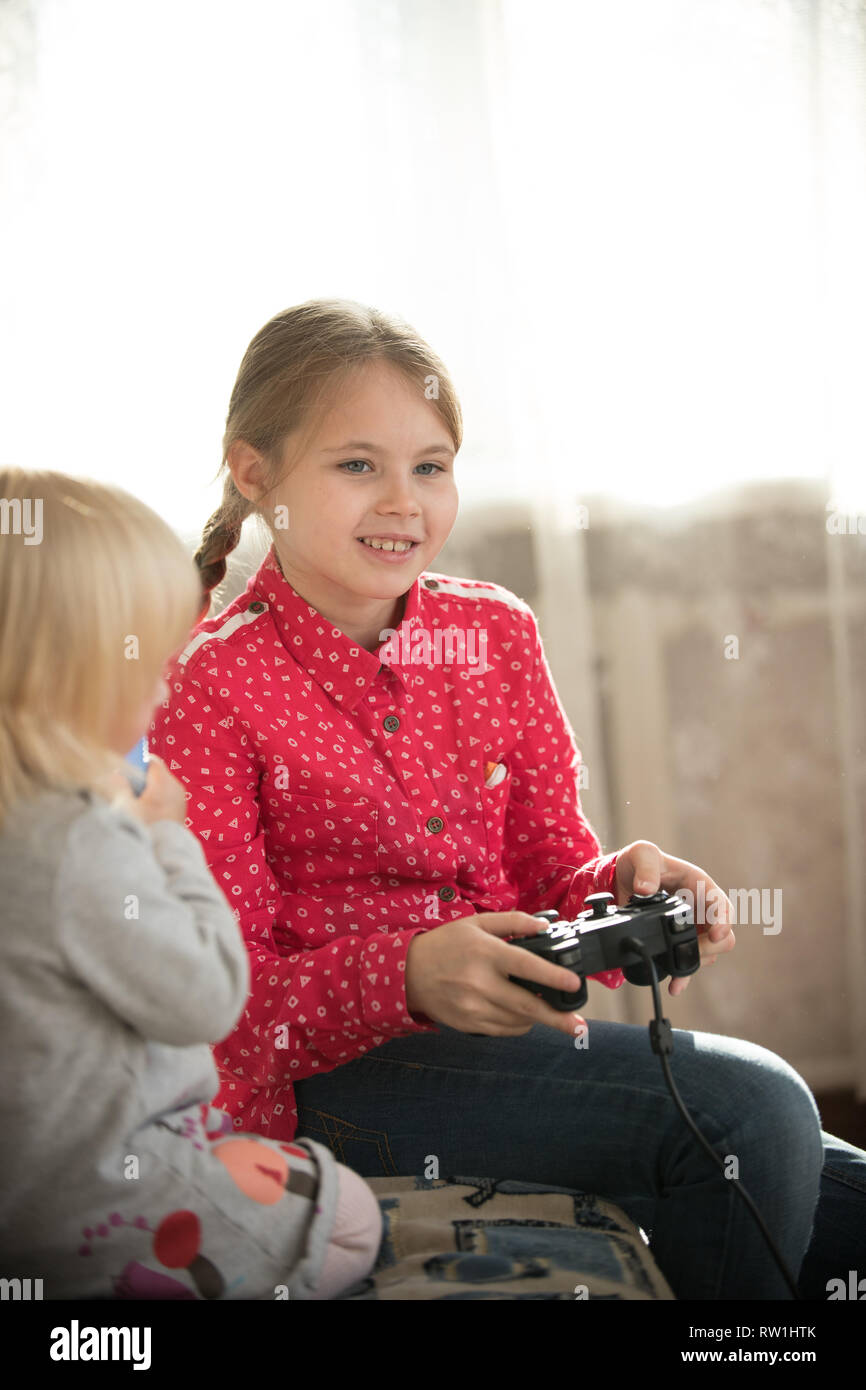 A girl holding a joystick and playing game - Stock Image
