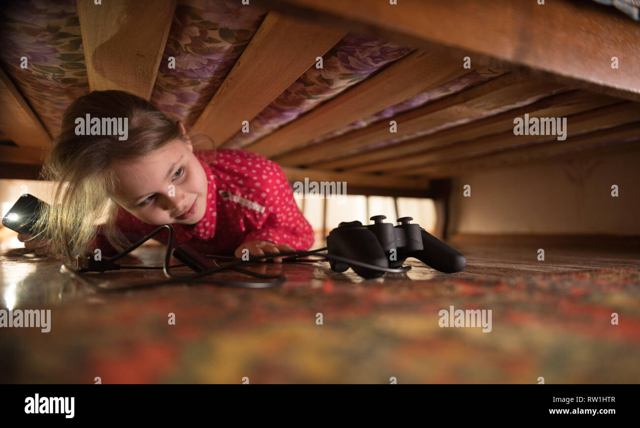 Joystick under the bed. Girl looking for it - Stock Image