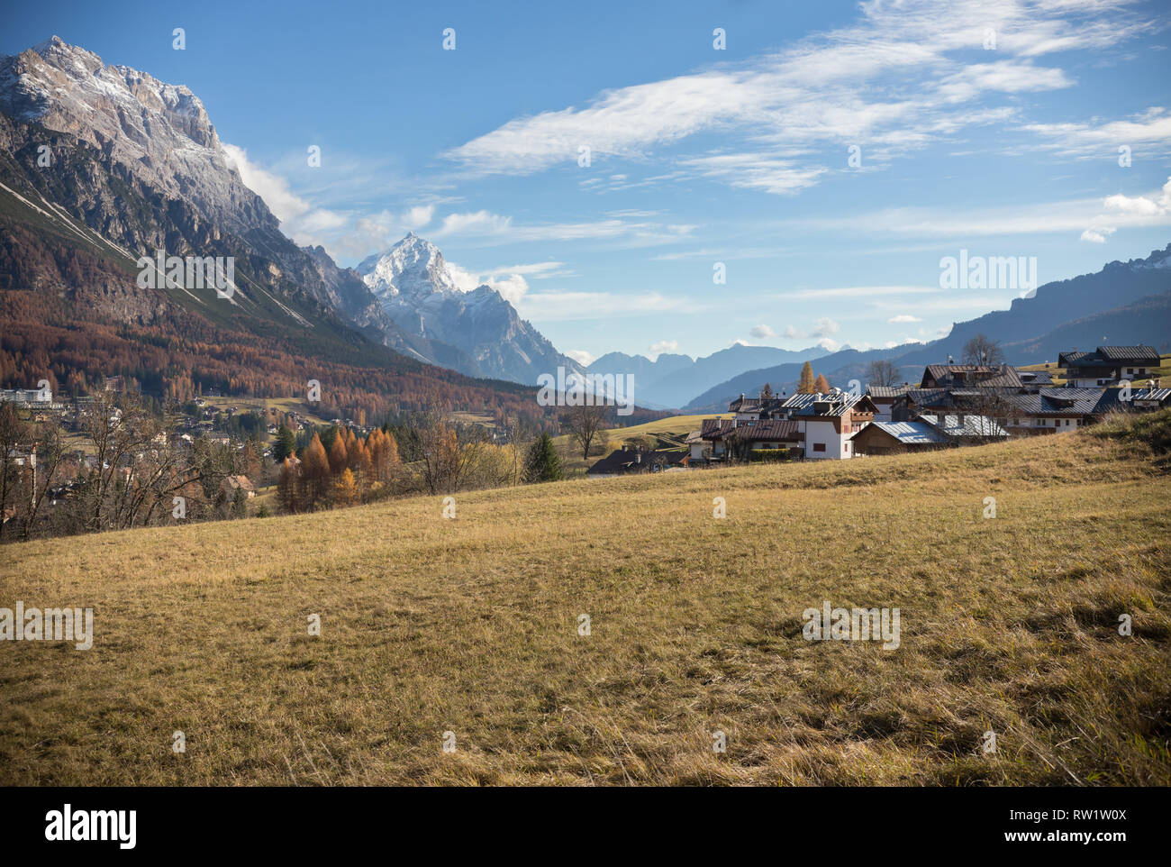 Dolomites nature. A yellow autumn field and country houses. Mid shot - Stock Image