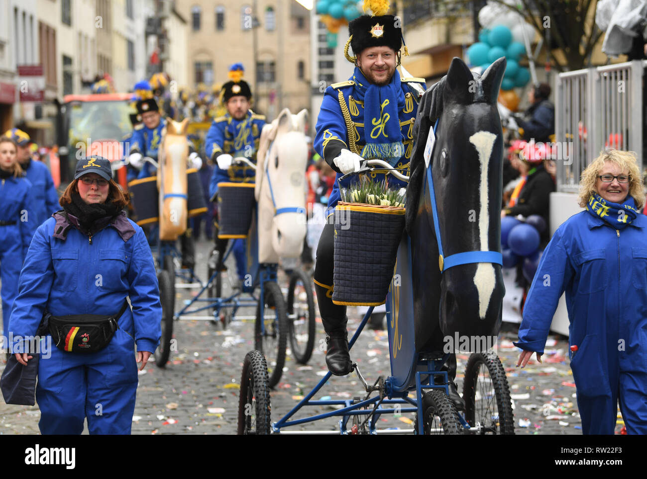 Cologne, Germany. 04th Mar, 2019. Cologne, Germany. 04th Mar, 2019.  Carnivalists of Treuer Husar blue-yellow v. 1925 ride bicycles at the Rosenmontagszug. Due to the weather, the people of Cologne had decided this time to do without horses and carriages in the train. With the Rose Monday processions, the Rhineland street carnival reaches its climax. Photo: Federico Gambarini/dpa Credit: dpa picture alliance/Alamy Live News - Stock Image
