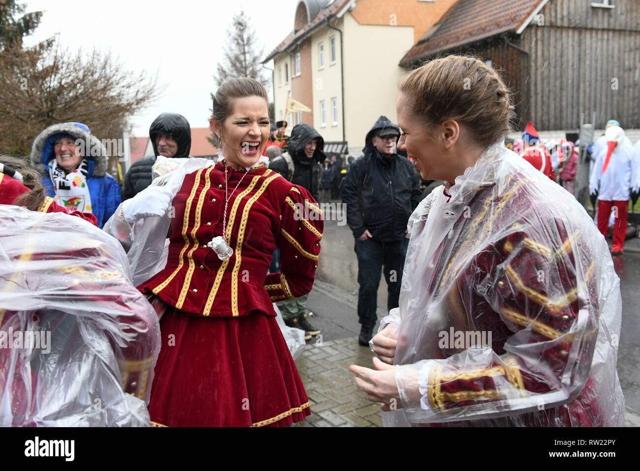 Herbstein, Germany. 04th Mar, 2019. Gardemädchen attract plastic ponchos before the beginning of the traditional jumper procession. The jumper train goes back to an old custom. In the 17th century, Tyrolean stonemasons brought this tradition to Herbstein. Credit: Uwe Zucchi/dpa/Alamy Live News - Stock Image