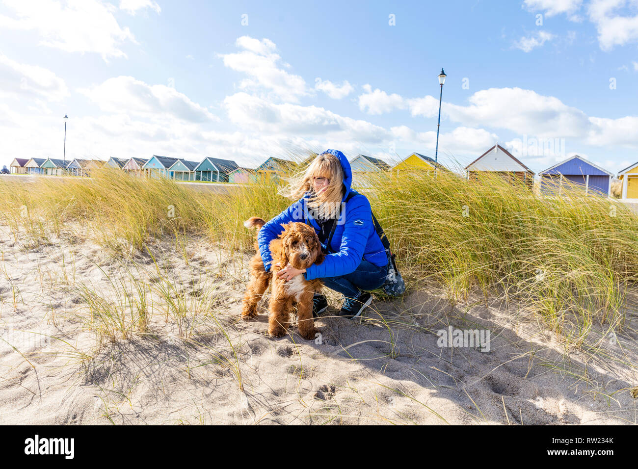 Sutton On Sea, Lincolnshire, UK. 04th Mar, 2019. UK Weather: 04/03/19 Bright, sunny but vwery windy day greats dog walker Lesley Thompson and Cockapoo Dexter on the sand dunes of Sutton On Sea, Lincolnshire, East coast, UK England. Clouds forming over the Chalets lining the sea front Credit: Tommy  (Louth)/Alamy Live News - Stock Image