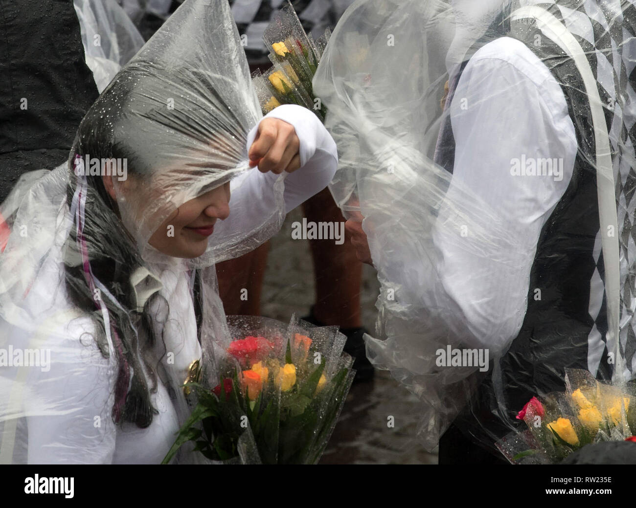 Cologne, Germany. 04th Mar, 2019. Cologne, Germany. 04th Mar, 2019.  Carnivalists protect themselves with transparent rain ponchos from the rain during the Rose Monday procession. With the Rose Monday processions, the Rhineland street carnival reaches its climax. Photo: Federico Gambarini/dpa Credit: dpa picture alliance/Alamy Live News - Stock Image